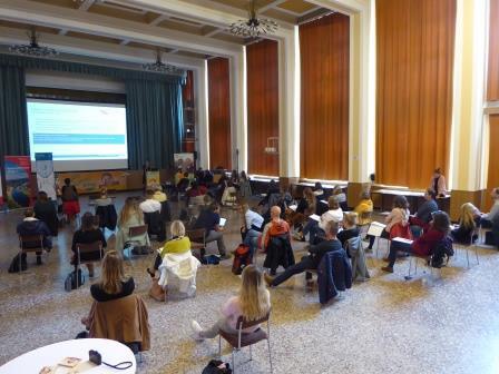 Tagungsgäste sitzen auf Stühlen vor einem großen Bildschirm mit einer Präsentation