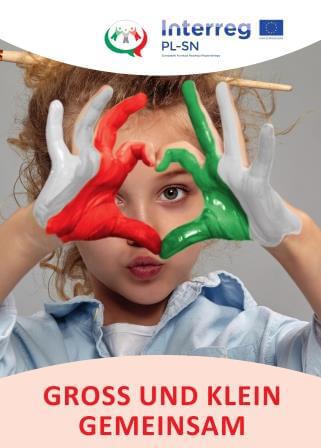 Foto zeigt Mädchen im Kitaalter, sie formt mit ihren Fingern ein Herz, die Hände sind mit Farbe bemalt