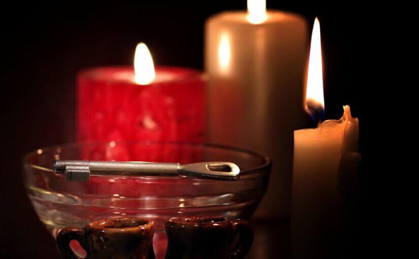 entzündete Kerzen stehen im Dunkeln, eine kleine Schüssel aus Glas steht davor, auf dessen Rand liegt ein Schlüssel