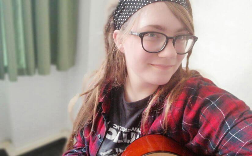 junge Frau mit Brille und Haarband und Gitarre in der Hand
