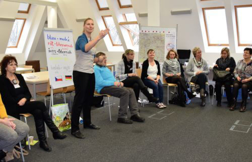 Bild zeigt einen Stuhlkreis mit mehreren Personen, eine Person erklärt stehend etwas gestikutiv